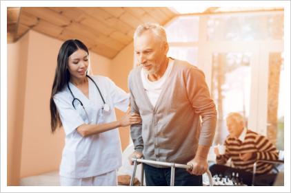 caregiver assisting elderly man to walk